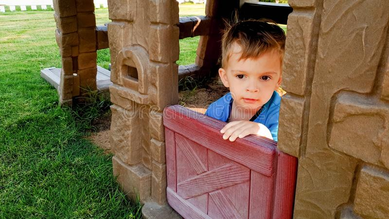 Πορτρέτο του λατρευτού παιχνιδιού αγοριών μικρών παιδιών στην παιδική χαρά με το πλαστικό σπίτι παιχνιδιών στο πάρκο στοκ εικόνες