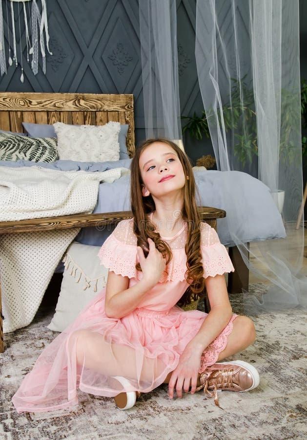 Πορτρέτο του λατρευτού χαμογελώντας παιδιού μικρών κοριτσιών στη συνεδρίαση φορεμάτων πριγκηπισσών σε ένα πάτωμα κοντά στο κρεβάτ στοκ εικόνα