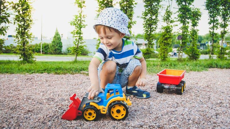 Πορτρέτο του λατρευτού χρονών παιχνιδιού αγοριών μικρών παιδιών 3 με το φορτηγό παιχνιδιών με το ρυμουλκό στην παιδική χαρά στο π στοκ εικόνα με δικαίωμα ελεύθερης χρήσης