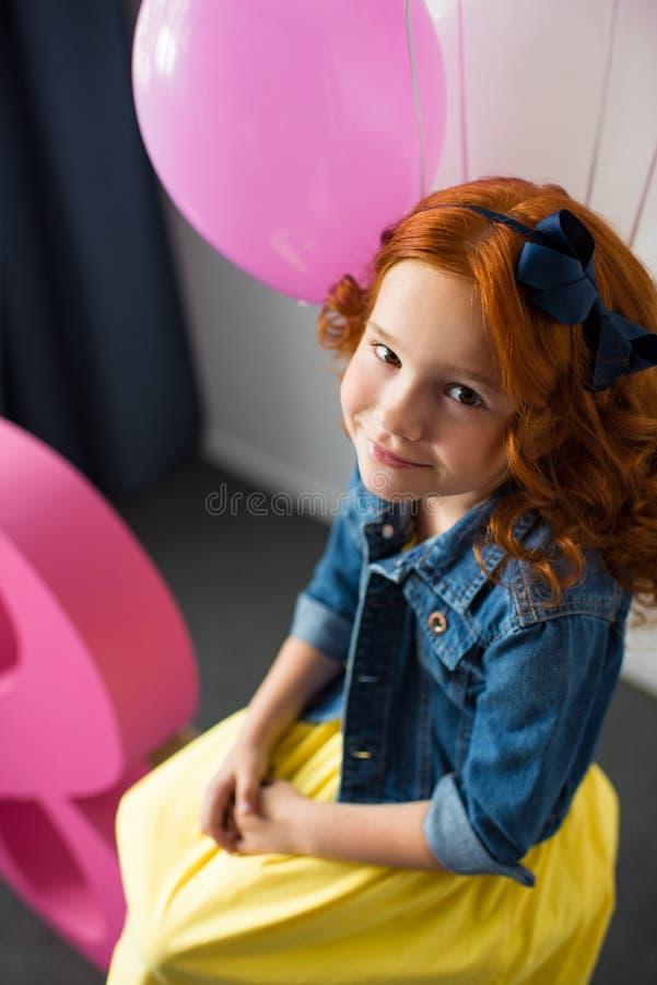 πορτρέτο του λατρευτού redhead χαμόγελου κοριτσιών στη κάμερα καθμένος στοκ φωτογραφία με δικαίωμα ελεύθερης χρήσης