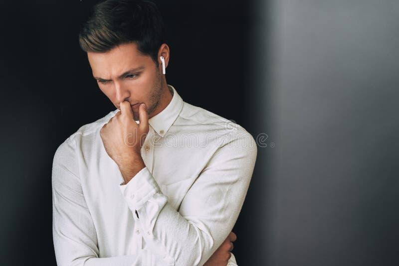 Πορτρέτο του λυπημένου νέου καυκάσιου όμορφου ατόμου που μιλά με έναν φίλο που χρησιμοποιεί τα ασύρματα ακουστικά, που θέτει στο  στοκ εικόνα
