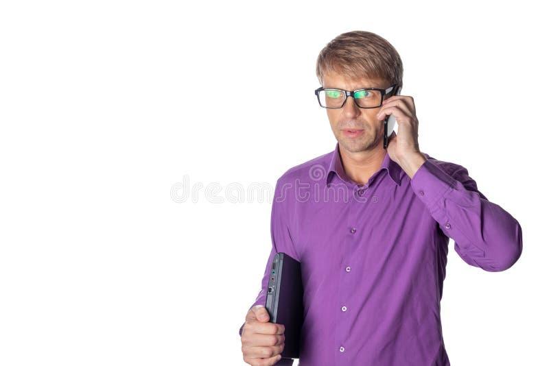 Πορτρέτο του μέσου ηλικίας τύπου που κρατά ένα lap-top και που μιλά στο κινητό τηλέφωνο πέρα από το άσπρο υπόβαθρο στοκ εικόνες με δικαίωμα ελεύθερης χρήσης