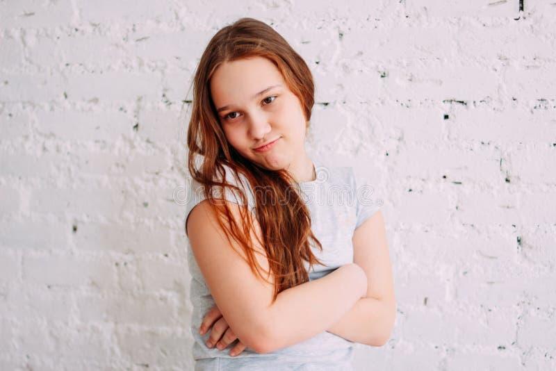 Πορτρέτο του μακριού κόκκινου χαριτωμένου κοριτσιού τρίχας στο άσπρο υπόβαθρο τοίχων στοκ φωτογραφία