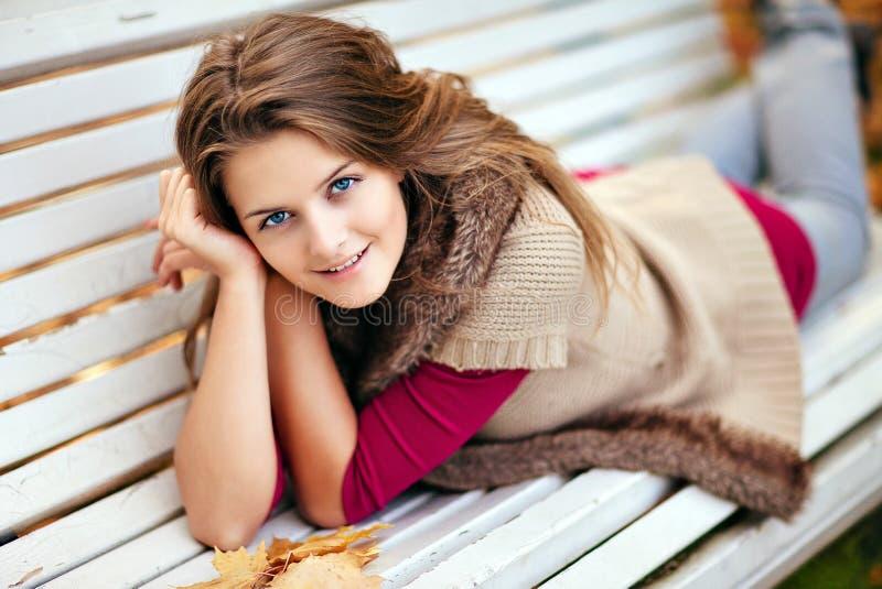 Πορτρέτο του μακρυμάλλους όμορφου κοριτσιού με τα φύλλα σφενδάμου στο autu στοκ φωτογραφία
