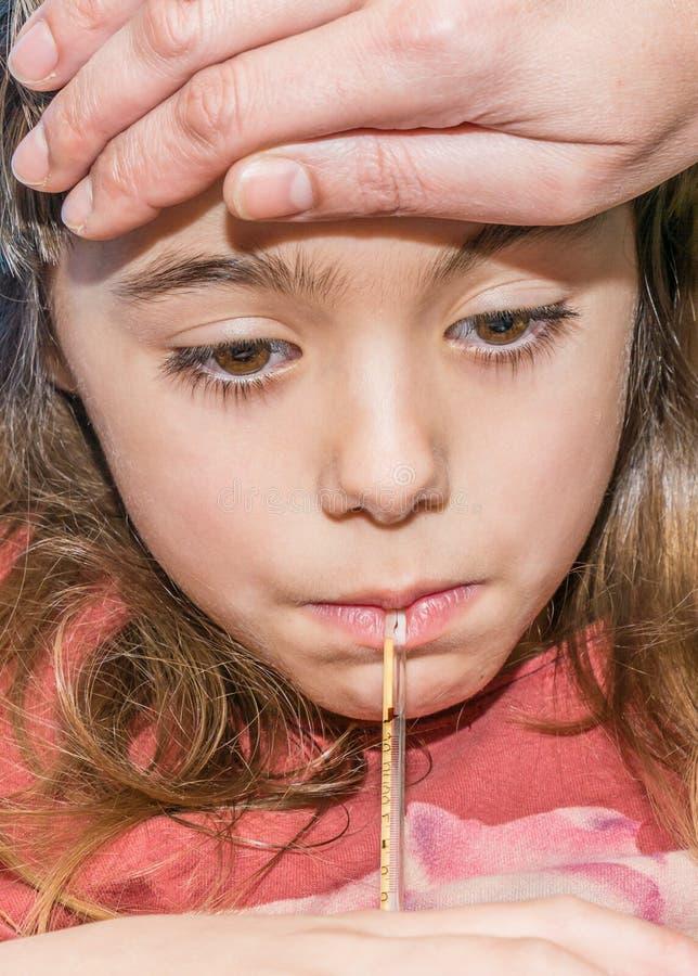 Πορτρέτο του μικρού άρρωστου κοριτσιού που μετρά τη θερμοκρασία στοκ φωτογραφίες