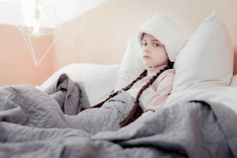 Πορτρέτο του μικρού άρρωστου κοριτσιού που περιορίζεται στο κρεβάτι στοκ φωτογραφίες