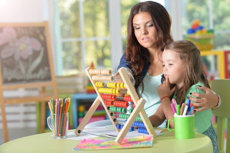 Πορτρέτο του μικρού κοριτσιού με τη μητέρα που χρησιμοποιεί τον άβακα στοκ εικόνα