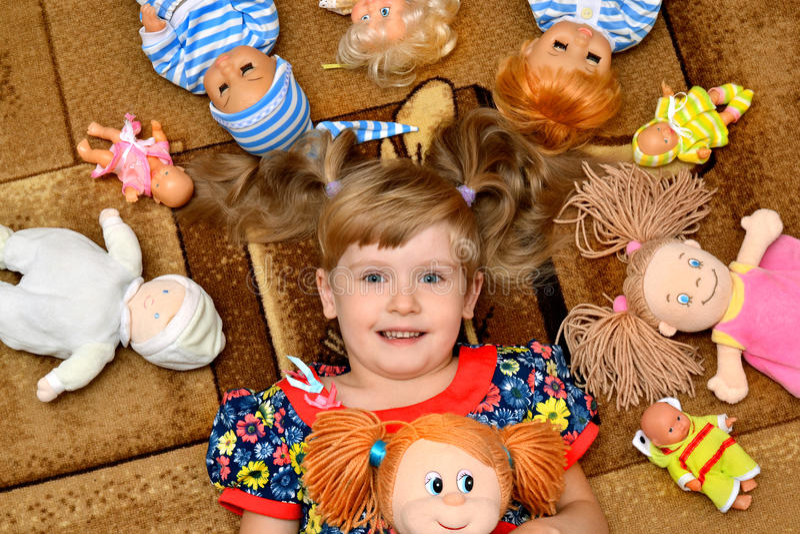 Πορτρέτο του μικρού κοριτσιού (παιδί, παιδί) με τις κούκλες στον τάπητα στοκ εικόνες