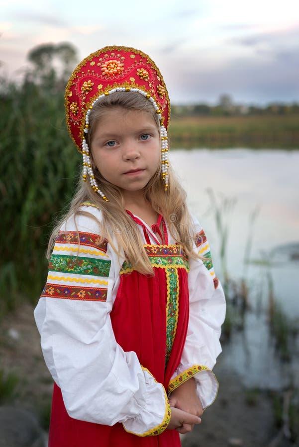 Πορτρέτο του μικρού κοριτσιού που ντύνεται στο ρωσικό εθνικό κοστούμι στο φυσικό υπόβαθρο στοκ φωτογραφία
