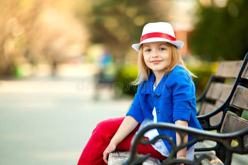 Πορτρέτο του μικρού κοριτσιού στον πάγκο σε ένα πάρκο στοκ φωτογραφίες με δικαίωμα ελεύθερης χρήσης