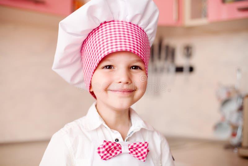 Πορτρέτο του μικρού παιδιού στο καπέλο του αρχιμάγειρα και μιας ποδιάς Λίγος αρχιμάγειρας μαγειρεύει στην κουζίνα Πορτρέτο του χα στοκ εικόνες