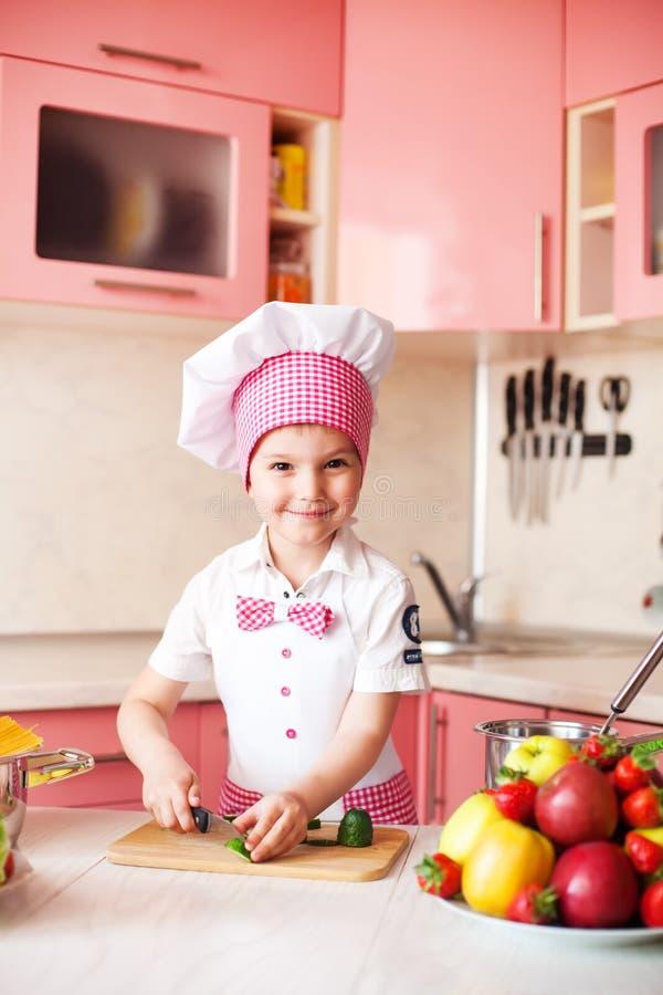 Πορτρέτο του μικρού παιδιού στο καπέλο του αρχιμάγειρα και μιας ποδιάς Λίγος αρχιμάγειρας μαγειρεύει στην κουζίνα Πορτρέτο του χα στοκ φωτογραφίες με δικαίωμα ελεύθερης χρήσης
