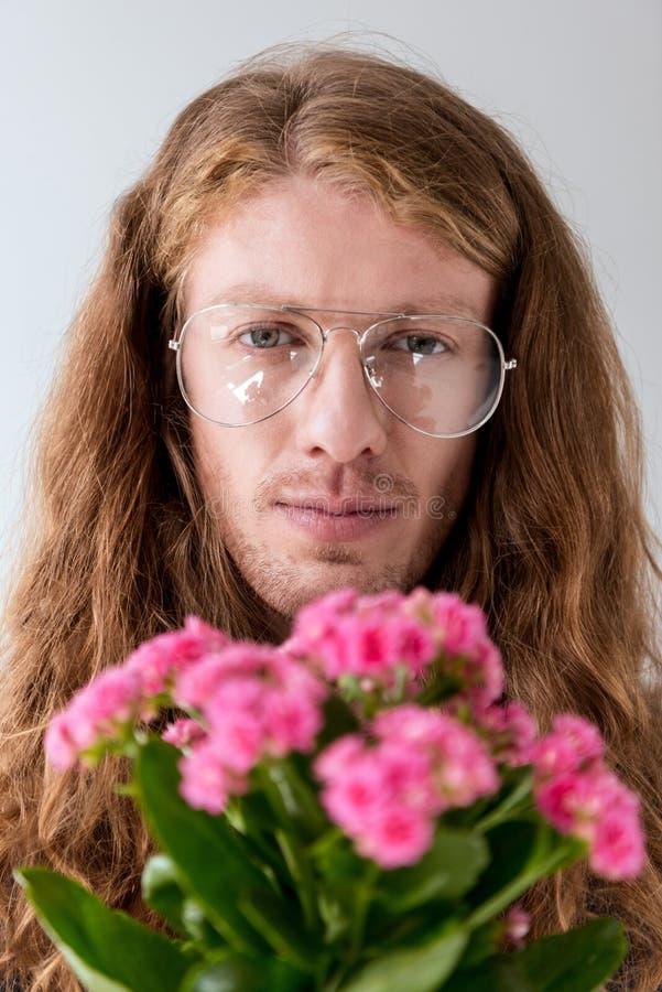 πορτρέτο του μοντέρνου ατόμου με τη σγουρή τρίχα με την ανθοδέσμη του ρόδινου κοιτάγματος λουλουδιών στοκ εικόνα