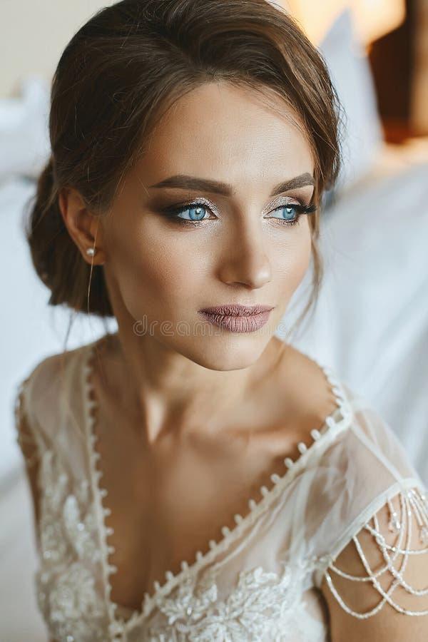 Πορτρέτο του μοντέρνου, όμορφου και αισθησιακού καφετής-μαλλιαρού πρότυπου κοριτσιού με το επαγγελματικά φωτεινά makeup και τα μπ στοκ εικόνα