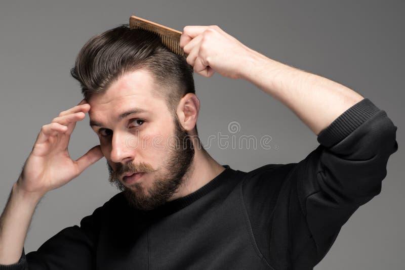 Πορτρέτο του μοντέρνου όμορφου νεαρού άνδρα που κτενίζει την τρίχα του στοκ φωτογραφία με δικαίωμα ελεύθερης χρήσης