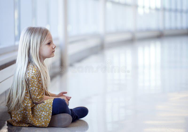 Πορτρέτο του μόνου μικρού κοριτσιού στην κίτρινη συνεδρίαση φορεμάτων στο πάτωμα στοκ εικόνα
