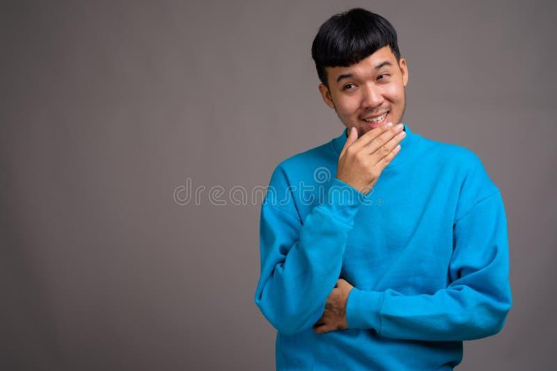 Πορτρέτο του νέου ασιατικού ατόμου στο γκρίζο κλίμα στοκ φωτογραφία με δικαίωμα ελεύθερης χρήσης