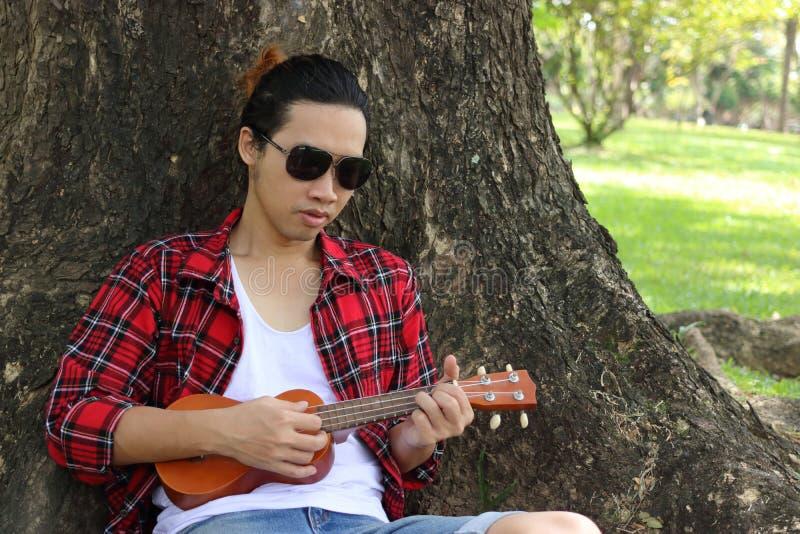 Πορτρέτο του νέου ατόμου hipster που παίζει ukulele στο υπόβαθρο φύσης στοκ εικόνα