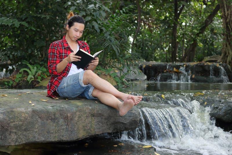 Πορτρέτο του νέου ατόμου hipster στο κόκκινο πουκάμισο που διαβάζει ένα βιβλίο στο όμορφο υπόβαθρο φύσης στοκ φωτογραφία με δικαίωμα ελεύθερης χρήσης