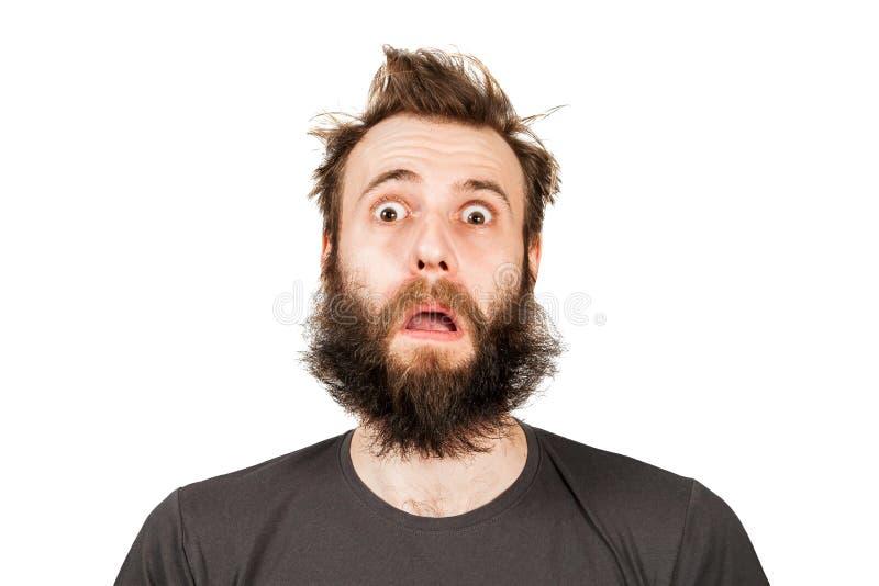 Πορτρέτο του νέου γενειοφόρου ατόμου με το ανοιγμένο στόμα και τα ευρέα μάτια Τύπος που απομονώνεται στο άσπρο υπόβαθρο στοκ φωτογραφία