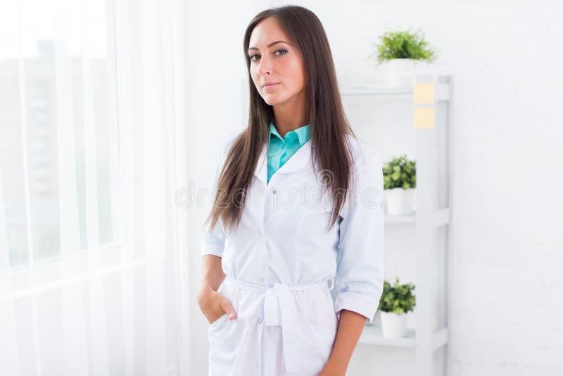 Πορτρέτο του νέου γιατρού γυναικών με το άσπρο παλτό που στέκεται στο ιατρικό γραφείο που εξετάζει τη κάμερα στοκ φωτογραφία