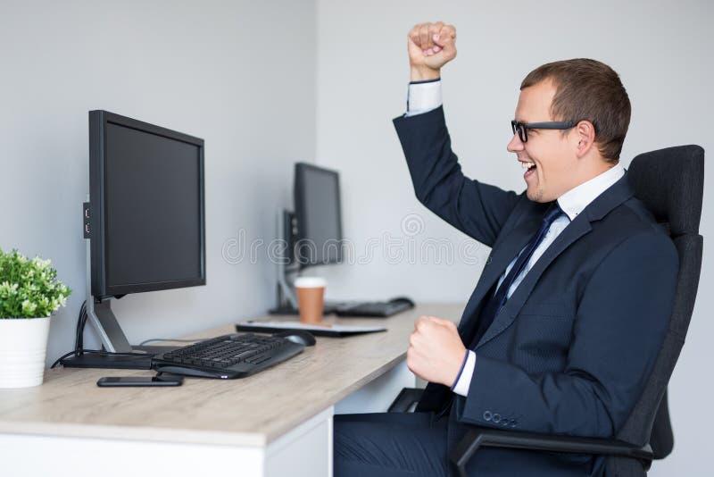 Πορτρέτο του νέου επιτυχούς επιχειρησιακού ατόμου που γιορτάζει κάτι στο σύγχρονο γραφείο στοκ εικόνες