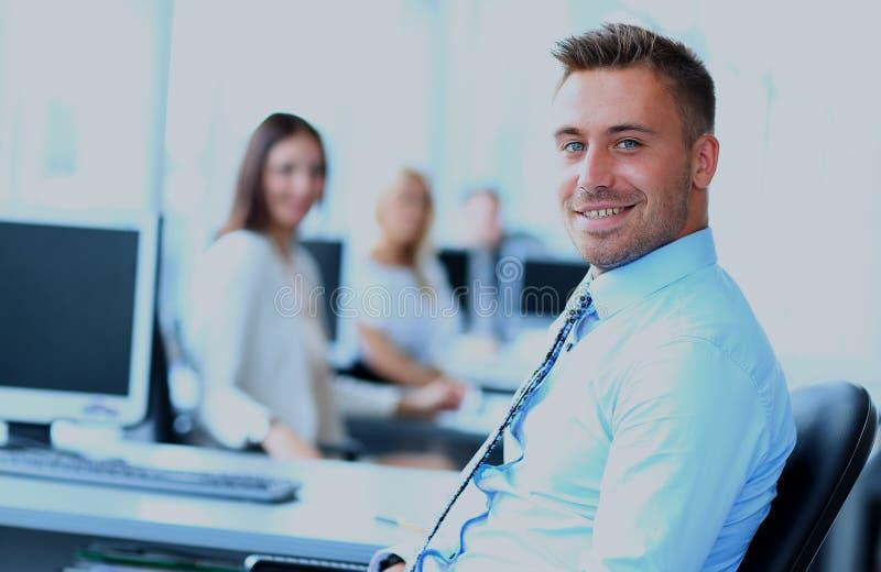 Πορτρέτο του νέου επιχειρηματία στην αρχή με τους συναδέλφους στο υπόβαθρο στοκ φωτογραφία