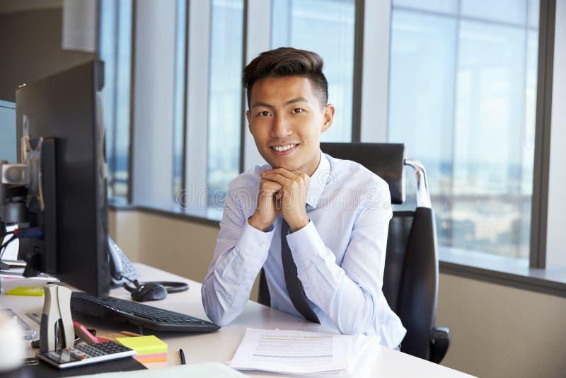 Πορτρέτο του νέου επιχειρηματία στο γραφείο γραφείων που χρησιμοποιεί τον υπολογιστή στοκ φωτογραφία