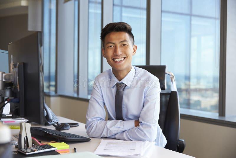 Πορτρέτο του νέου επιχειρηματία στο γραφείο γραφείων που χρησιμοποιεί τον υπολογιστή στοκ φωτογραφία με δικαίωμα ελεύθερης χρήσης