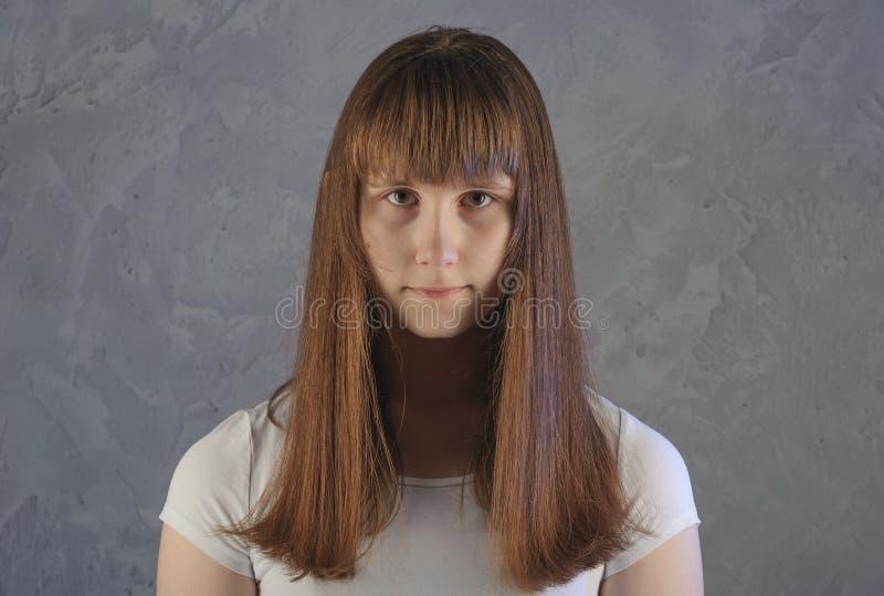 Πορτρέτο του νέου ευρωπαϊκού θηλυκού που εξετάζει τη κάμερα με σοβαρό στοκ εικόνες
