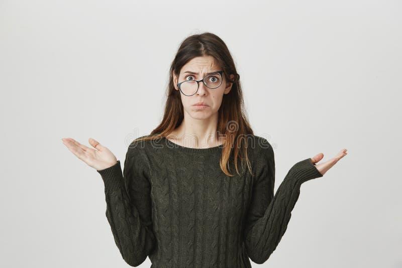 Πορτρέτο του νέου ευρωπαϊκού σπουδαστή στο σκούρο πράσινο πουλόβερ με την ταραγμένη και θλιβερή έκφραση, που φορά τα γυαλιά και στοκ εικόνα με δικαίωμα ελεύθερης χρήσης