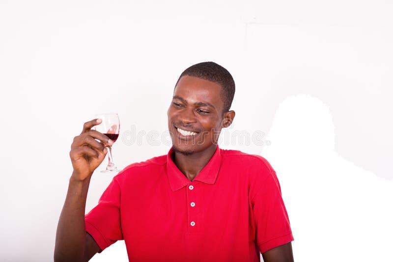 Πορτρέτο του νέου ευτυχούς ατόμου που κρατά ένα ποτήρι του κόκκινου κρασιού στοκ εικόνα με δικαίωμα ελεύθερης χρήσης