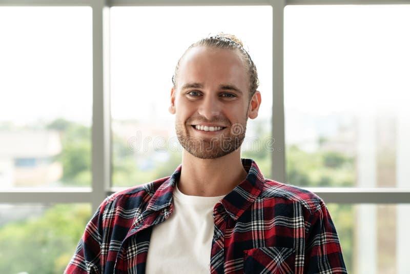 Πορτρέτο του νέου ευτυχούς κοντού μοντέρνου γενειοφόρου καυκάσιου ατόμου ή του δημιουργικού σχεδιαστή που χαμογελά και που εξετάζ στοκ εικόνες