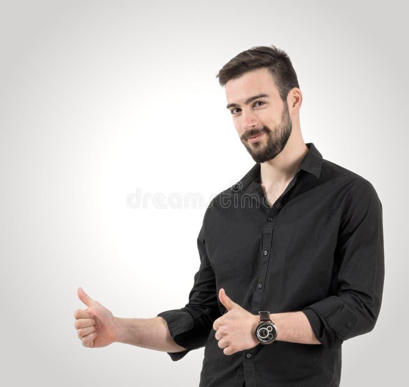 Πορτρέτο του νέου ευτυχούς χαμογελώντας ατόμου με τους αντίχειρες επάνω στη χειρονομία στοκ φωτογραφία με δικαίωμα ελεύθερης χρήσης