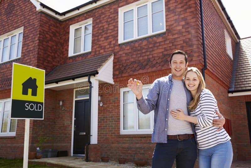 Πορτρέτο του νέου ζεύγους με τα κλειδιά για το νέο σπίτι στοκ εικόνα