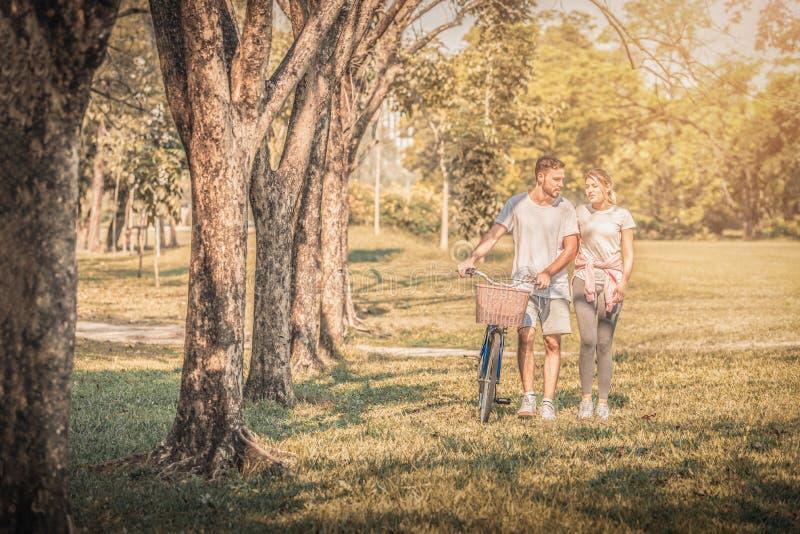 Πορτρέτο του νέου ζεύγους που απολαμβάνει στο πάρκο στο ηλιοβασίλεμα Έννοια ρομαντική και αγάπη Θερμός τόνος στοκ εικόνες