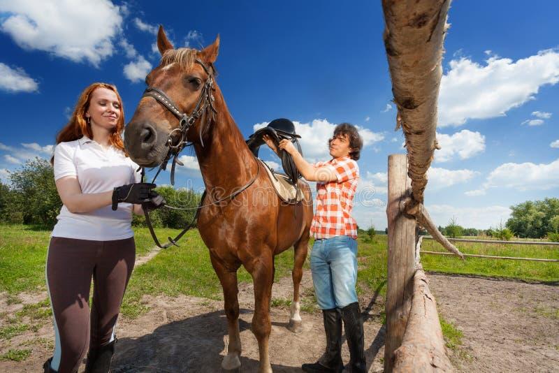 Πορτρέτο του νέου ζεύγους που φορτώνει το άλογο κόλπων τους στοκ εικόνες