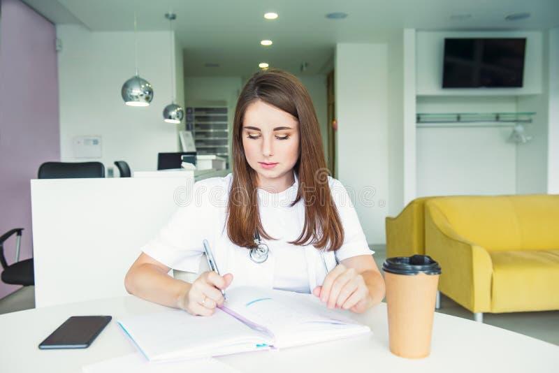 Πορτρέτο του νέου θηλυκού γιατρού που κάνει τις σημειώσεις στο σημειωματάριο καθμένος πίσω από τον πίνακα με το τηλέφωνο και τον  στοκ φωτογραφίες με δικαίωμα ελεύθερης χρήσης
