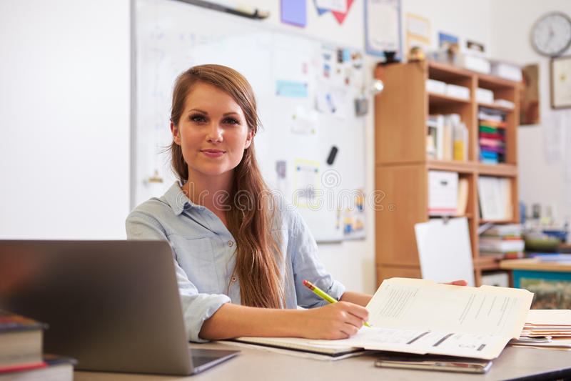 Πορτρέτο του νέου θηλυκού δασκάλου στο γραφείο που κοιτάζει στη κάμερα στοκ εικόνα με δικαίωμα ελεύθερης χρήσης