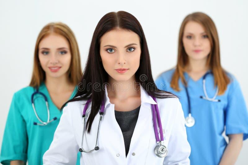 Πορτρέτο του νέου θηλυκού γιατρού brunette που περιβάλλεται από τη ιατρική ομάδα στοκ φωτογραφίες