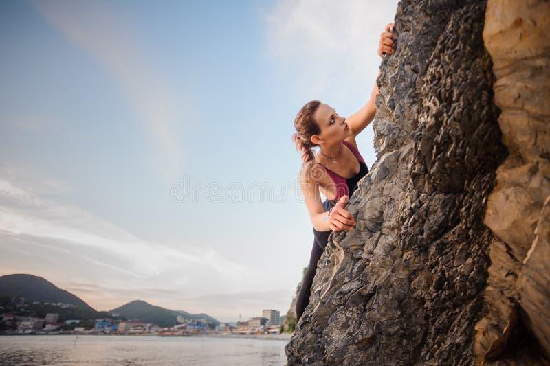 Πορτρέτο του νέου θηλυκού overhanging απότομου βράχου ορειβατών βράχου Κρατώντας το σχοινί και κοιτάζοντας κάτω Όμορφος μπλε ουρα στοκ εικόνα