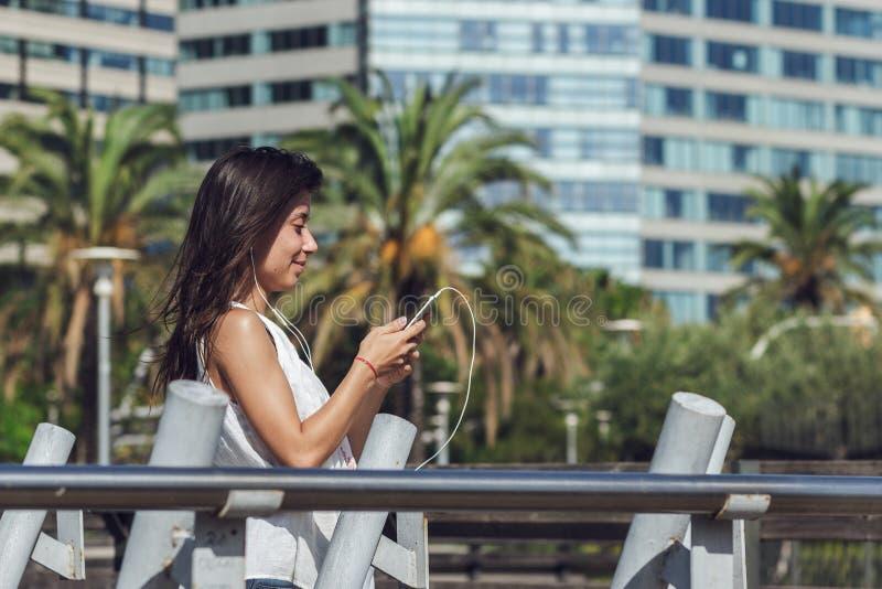 Πορτρέτο του νέου κοριτσιού που διαβάζει ένα μήνυμα στο smartphone της πέρα από το υπόβαθρο πόλεων στοκ εικόνες με δικαίωμα ελεύθερης χρήσης