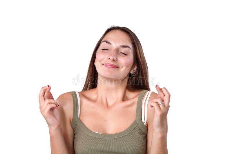 Πορτρέτο του νέου κοριτσιού που στέκεται πέρα από το άσπρο υπόβαθρο, που κρατά τα δάχτυλα διασχισμένα για την καλή τύχη στοκ εικόνα με δικαίωμα ελεύθερης χρήσης