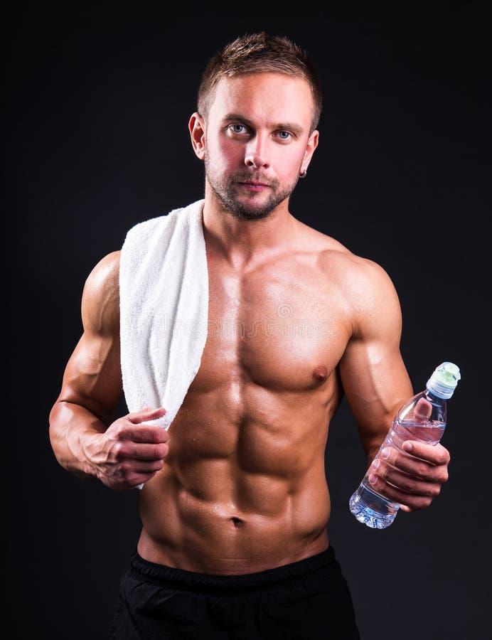 Πορτρέτο του νέου μυϊκού ατόμου που στέκεται πέρα από το γκρι με την πετσέτα και στοκ εικόνα