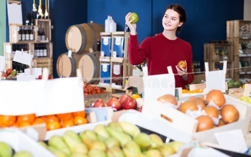 Πορτρέτο του νέου πελάτη που επιλέγει το μήλο στο παντοπωλείο στοκ εικόνες