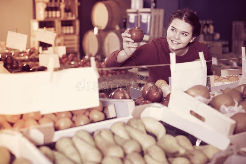 Πορτρέτο του νέου πελάτη που επιλέγει το μήλο στο παντοπωλείο στοκ εικόνα με δικαίωμα ελεύθερης χρήσης