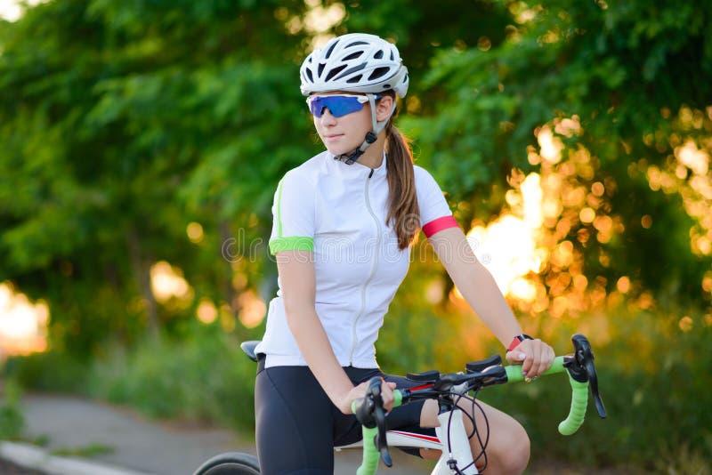 Πορτρέτο του νέου ποδηλάτη γυναικών που στηρίζεται με το ποδήλατο στο ηλιοβασίλεμα Αθλητισμός και υγιής έννοια τρόπου ζωής στοκ εικόνα με δικαίωμα ελεύθερης χρήσης