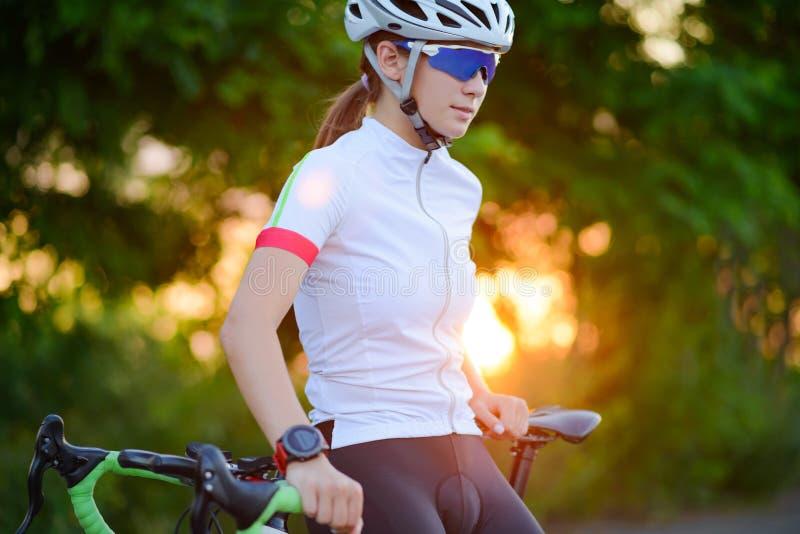 Πορτρέτο του νέου ποδηλάτη γυναικών που στηρίζεται με το ποδήλατο στο ηλιοβασίλεμα Αθλητισμός και υγιής έννοια τρόπου ζωής στοκ εικόνα