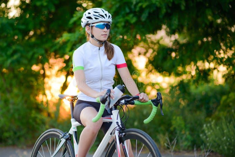 Πορτρέτο του νέου ποδηλάτη γυναικών που στηρίζεται με το ποδήλατο στο ηλιοβασίλεμα Αθλητισμός και υγιής έννοια τρόπου ζωής στοκ φωτογραφία