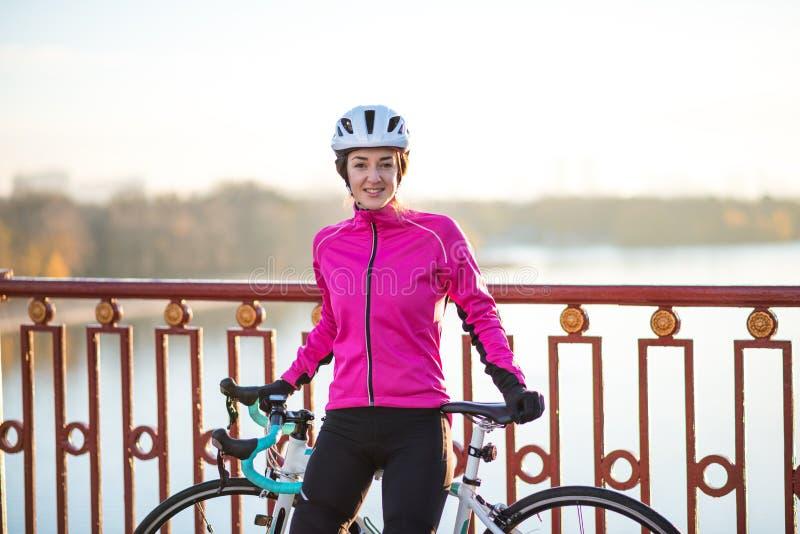Πορτρέτο του νέου χαμογελώντας θηλυκού ποδηλάτη στο ρόδινο σακάκι που στηρίζεται με το οδικό ποδήλατο στην κρύα ηλιόλουστη ημέρα  στοκ φωτογραφίες με δικαίωμα ελεύθερης χρήσης